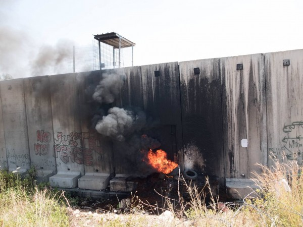 Fire at the Apartheid wall away from the main protest
